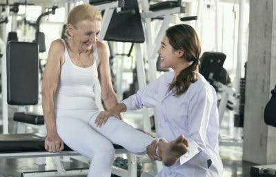 therapist stretching the leg of a patient with muscle weakness after frontal lobe stroke