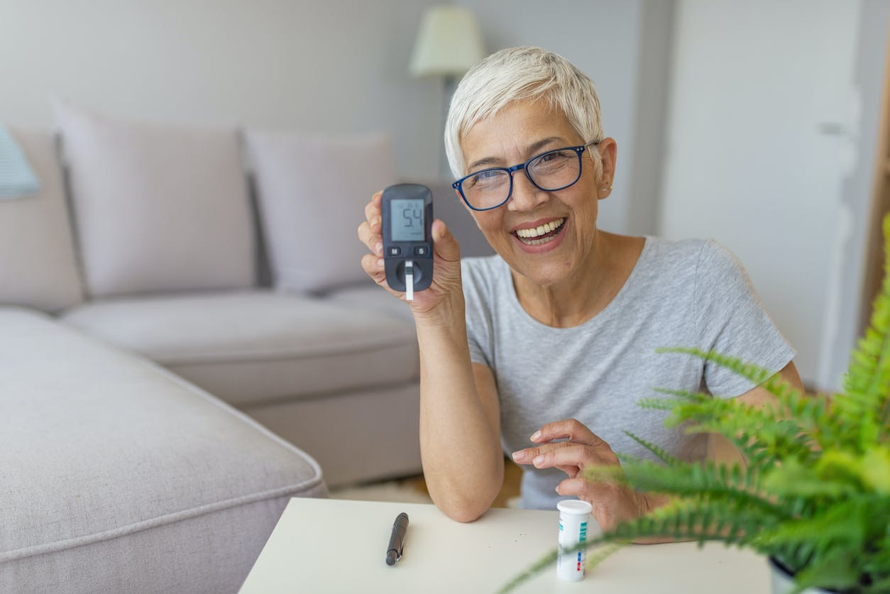 woman smiling and checking blood sugar level at home