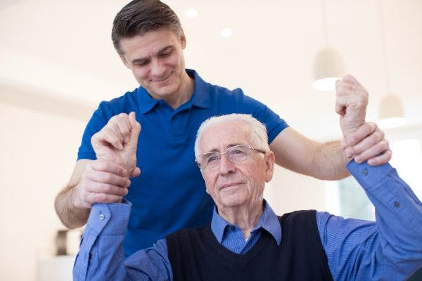 Physical therapist raising stroke patient's arms to help him overcome flaccidity after stroke