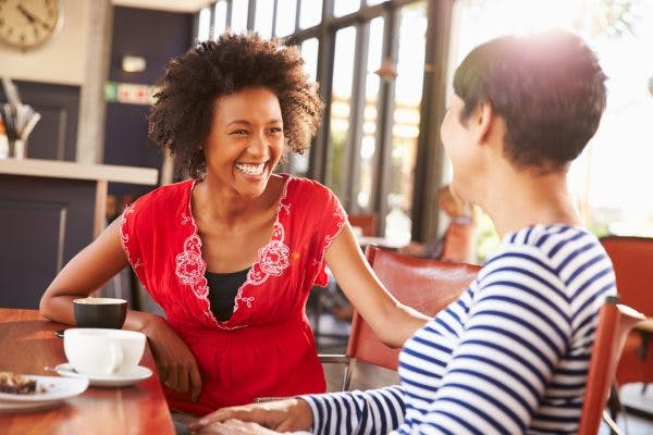 smiling woman talking to someone with brain injury in coffee shop