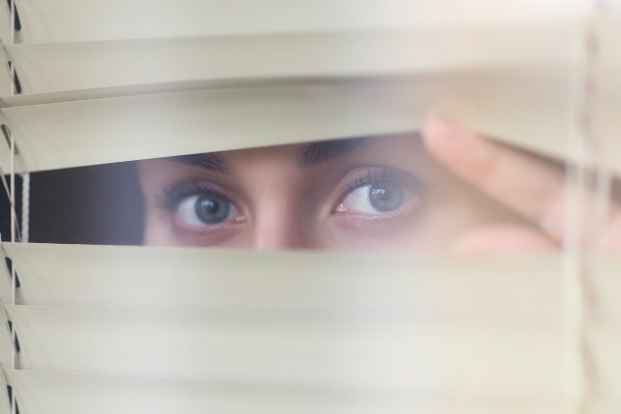 woman's eyes peeking through blinds