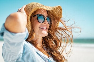 woman with sun hat and summer blouse smiling on beach