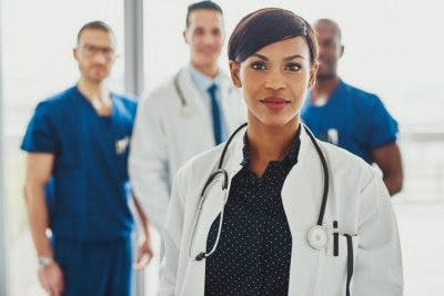 group of confident doctors in white coats and scrubs
