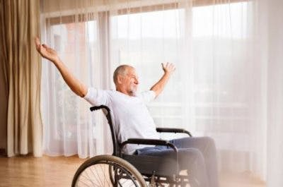 man in wheelchair practicing active stroke exercises at home
