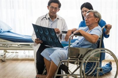 doctor showing SCI patient spinal xrays