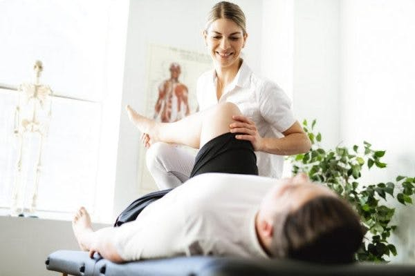physical therapist helping client stretch contractures after brain injury