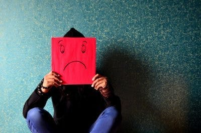 person sitting in front of dark blue wall holding a square red piece of paper with a sad face drawn on it over their face to represent depression