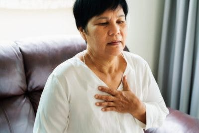 woman putting hand on chest and breathing hard because she has autonomic dysfunction