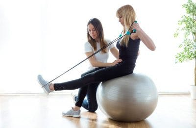 woman sitting on exercise ball and stretching foot