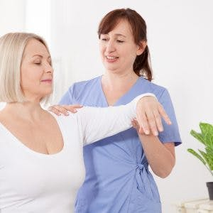 physiotherapist helping a stroke patient to use compensatory strategies safely