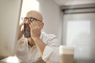 man rubbing eyes while sitting at desk because he has fatigue, a symptom of hypothalamus brain damage