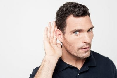 man putting hand behind ear because he can't hear