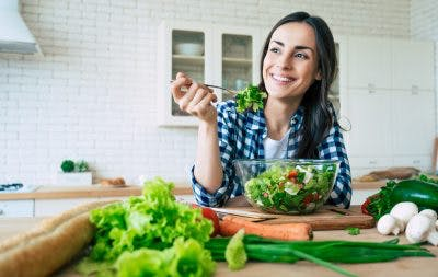 woman smiling and eating salad