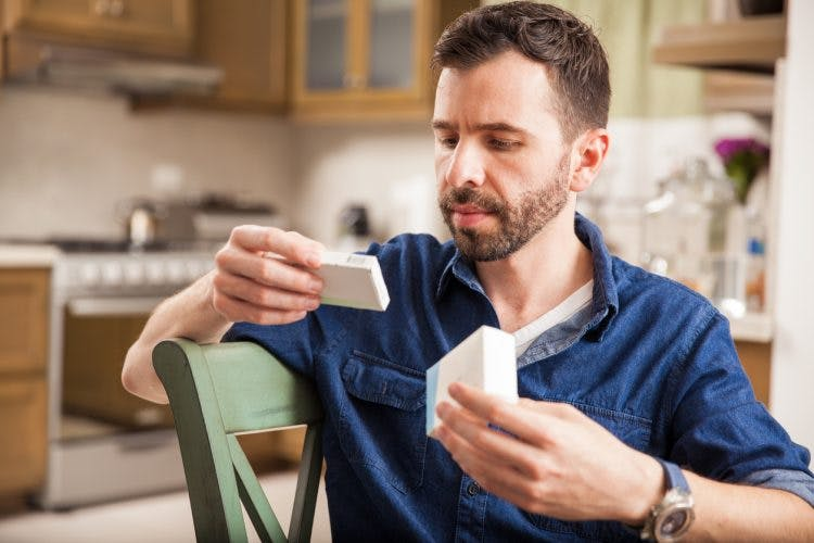 man sitting at kitchen table reading label of Adderall for TBI
