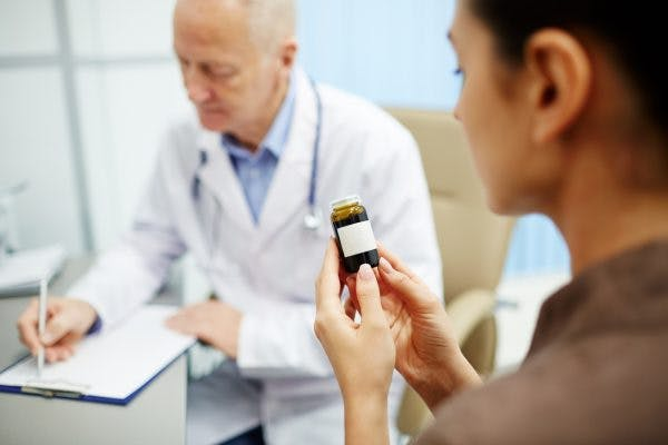 woman reading label of bottle of aricept for brain injury while doctor writes instructions in the background