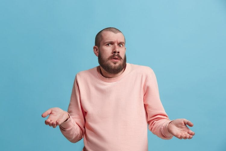 Man shrugging and looking confused because he has false memories after brain injury