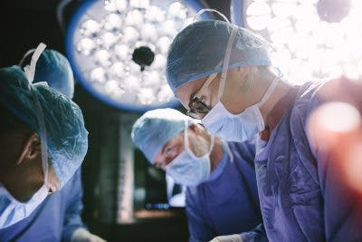 Concentrated surgeon performing craniotomy with her team