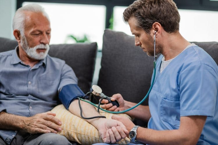 Doctor manually measuring blood pressure of patient who may have high blood pressure after head injury