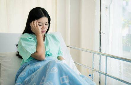 Frau, die mit Kopfschmerzen im Krankenhausbett kämpft