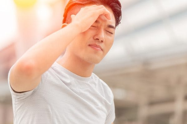Man holding head squinting in bright sunlight because he has light sensitivity after brain injury