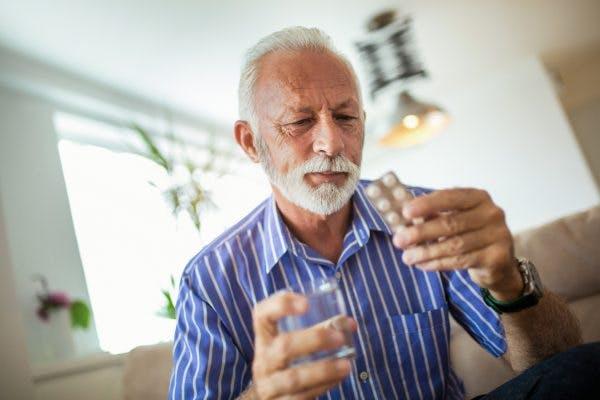 Senior man tat home taking memantine pills for TBI