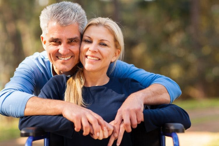 mid age man and disabled wife smiling about their relationship after traumatic brain injury