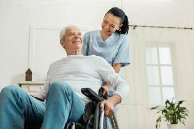 Physiotherapeut hilft Schlaganfallpatienten im Rollstuhl