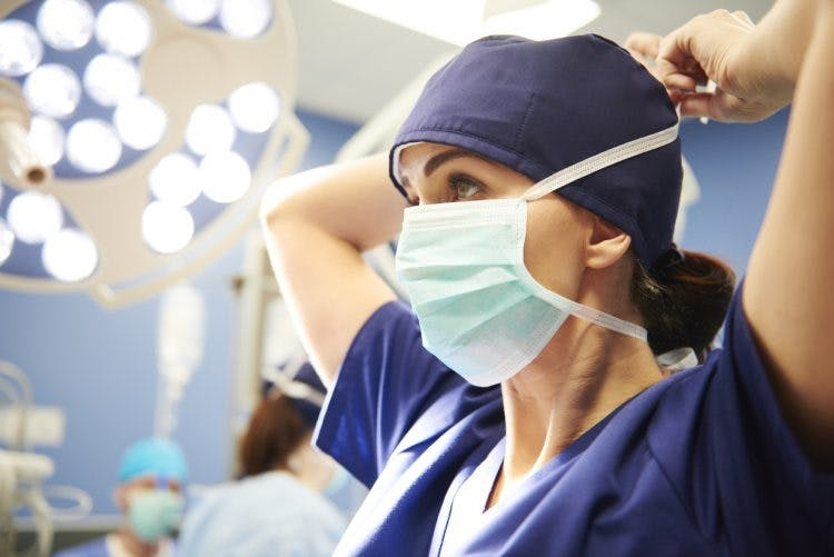 Side view of young female surgeon tying her surgical mask, discussing the types of surgery for head injury with her colleagues