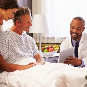 Doctor talking to male patient and wife in hospital bed about what to expect after brain injury