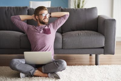 man sitting on living room floor with laptop, smiling and putting hands behind head