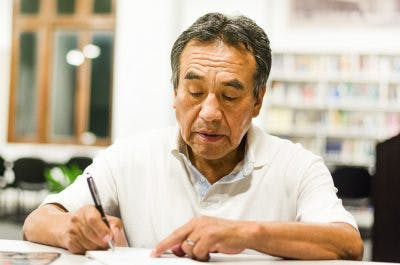 senior man writing in notebook in library