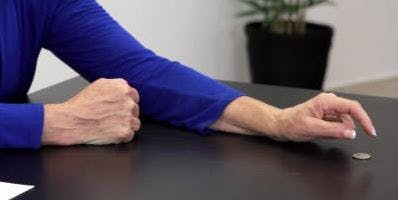 therapist placing a quarter down on the table for hand therapy