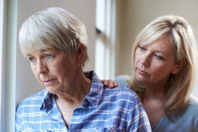 adult daughter comforting elderly mother who has flat affect after brain injury