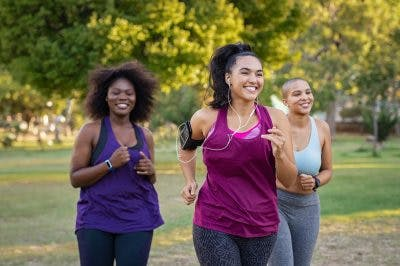 Three women jogging together in park to stay fit
