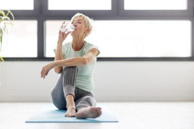 woman sitting on exercise mat drinking water