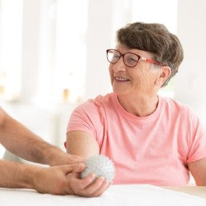 physical therapist placing hand therapy ball into stroke patients hand in clinic setting