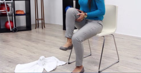 therapist in chair demonstrating leg exercises for stroke patients