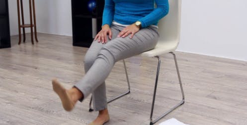 therapist in chair with right leg extended