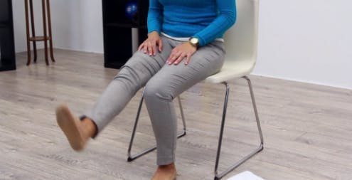 physical therapist in chair with left leg extended for rehab exercise