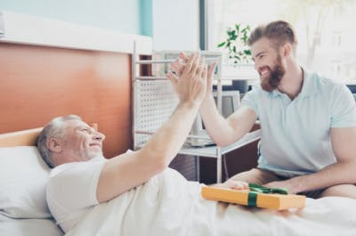 young adult grandson visiting grandpa in hospital, giving him high five