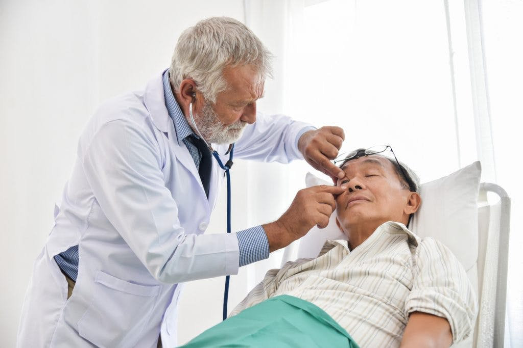 Doctor checking man for brain stem injury recovery signs.