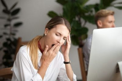 woman sitting at computer and yawning