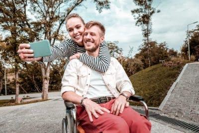 girlfriend taking selfie with her boyfriend in a wheelchair