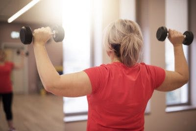 woman doing shoulder press in gym