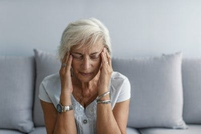 senior woman sitting on couch rubbing temples and closing her eyes