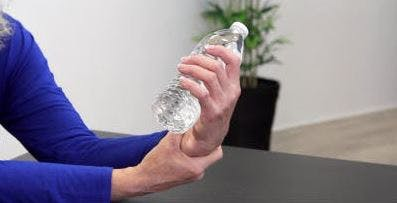 therapist holding water bottle in hand like a dumbbell