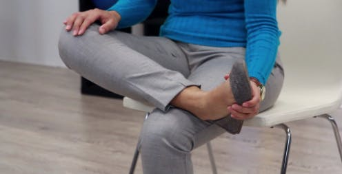 physical therapist with crossed legs using hand to lift foot up towards body