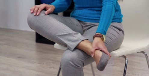 physical therapist with crossed legs using hand to lift up foot drop exercise