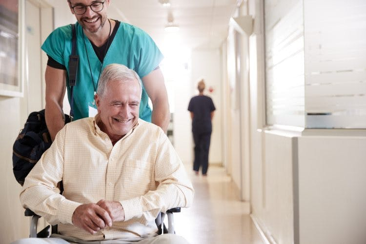 Man being pushed in wheelchair smiling because he is leaving the hospital after stroke