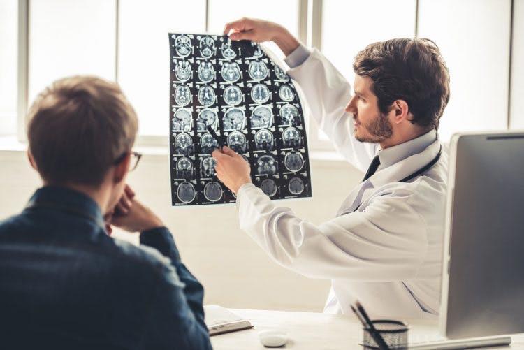 Der Neurologe hält Gehirnscans hoch, um zu diskutieren, warum Patienten nach einem Schlaganfall nicht sprechen können
